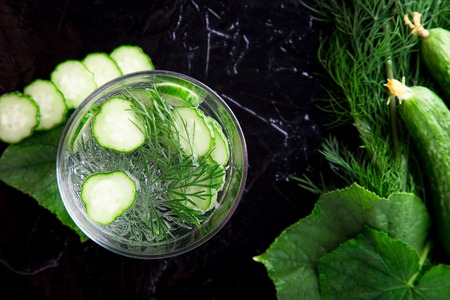 Cucumber water in glass with dill on black background. Detox, diet. Backlight. Top view. Copy space