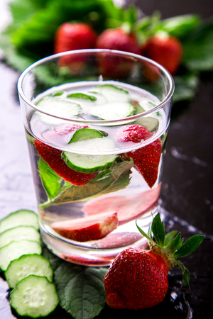 infused: Cucumber and strawberry detox water in glass on black background. Backlight. Diet