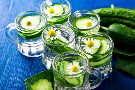 Cucumber water in six little mason glass jar on blue background. Rustic. Detox