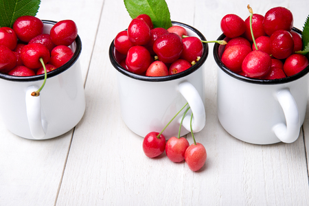 Cherry in enamel cup on white wooden background. Healthy, summer fruit. Cherries Stock Photo
