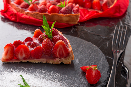 powdered: Strawberry pie on black slate plate. One piece. Close up Stock Photo