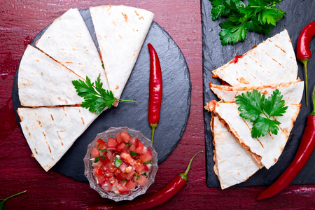 Mexican quesadilla with salsa on black slate stone plate on red wooden background. Chili pepper. Top view