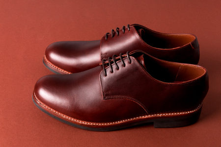 Brown oxford shoes on red background. Close up