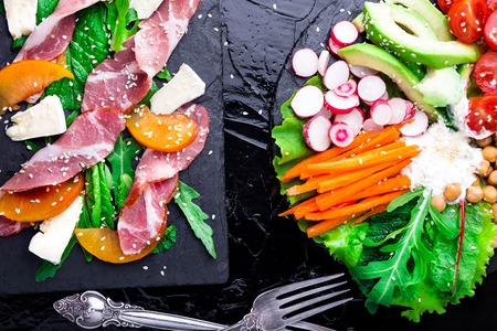 Two different salads om black stone slate. Vegan salad. Meat salad. Salad with ham jamon serrano, camembert, melon, arugula. Top view