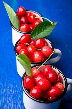 Cherry in enamel cup on blue wooden background. Healthy, summer fruit. Cherries