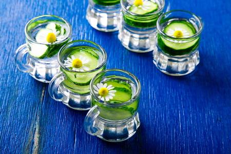 Cucumber water in six little mason glass jar on blue background. Rustic. Detox.