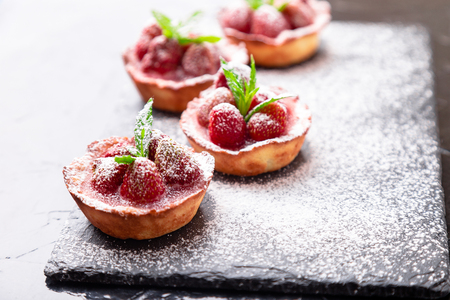 Homemade strawberries tarts with powdered sugar on slate plate, black background. Close up Archivio Fotografico