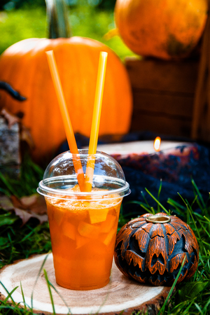 terrifying: Halloween cocktail with pumpkins decoration on background. Punch for a party. Jack-o-Lantern. Close up Stock Photo