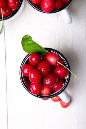Cherry in enamel cup on white wooden background. Healthy, summer fruit. Cherries. Top view Stock Photo