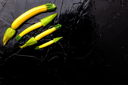 Yellow small zucchinis with flower on black background. Top view.  Frame. Copy space