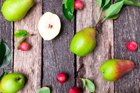 Pear and small apple on wooden rustic background. Top view. Frame. Autumn harvest