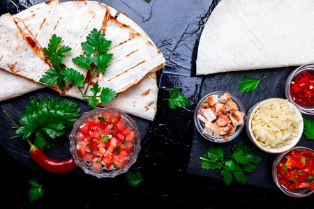 Mexican quesadilla and ingredients with salsa on black slate stone plate. Top view