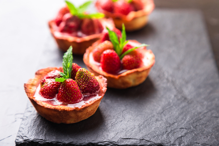 Homemade strawberries tarts on slate plate, black background. Stock fotó