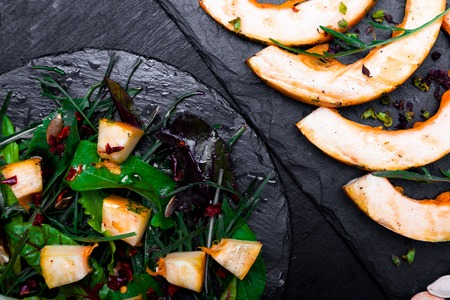 Warm pumpkin salad with mixed leaf of arugula, chard, in on black slate plate on black background. Grilled pumpkin. Top view. Stock Photo