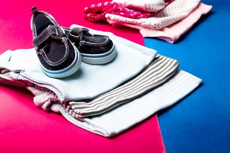 baby stuff: Folded blue and pink bodysuit with boat shoes on it on minimalistic pink and blue background. diaper for newborn boy and girl. Stack of infant clothing. Child outfit.