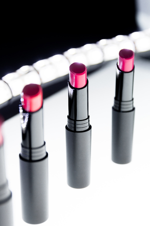 Set of matte Lipstick in red and natural colors on white and black background. Fashion colorful lipsticks. Professional makeup and beauty. Blinking bokeh background