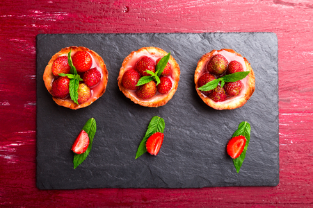 Homemade strawberries tarts on slate plate, black background. Top view