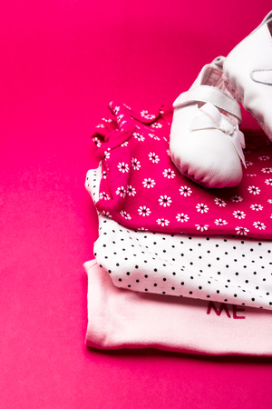 baby stuff: Folded pink bodysuit with shoes on it on minimalistic pink background. diaper for newborn girl. Stack of infant clothing. Child outfit. Stock Photo