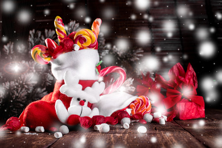Christmas socks full of candy and sweets on wooden background