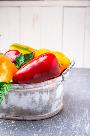 Red and Yellow Bell Peppers in grey basket. Healthy Organic Vegetables. Close up Stock Photo