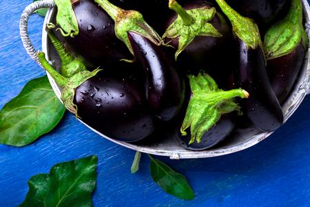 グレー バスケット ブルー木製テーブルの上に新鮮な茄子。素朴な背景。平面図です。領域をコピーします。ビーガン野菜