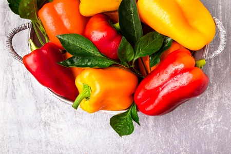 Red and Yellow Bell Peppers in grey basket. Healthy Organic Vegetables. Top view Stock Photo