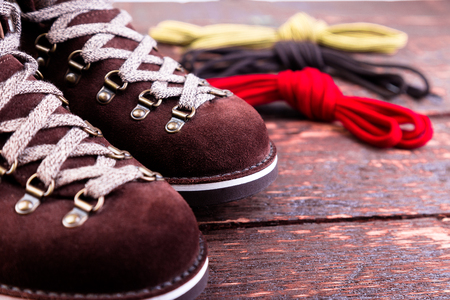Brown man suede boots and shoelaces on wooden background. Autumn or winter shoes. Macro