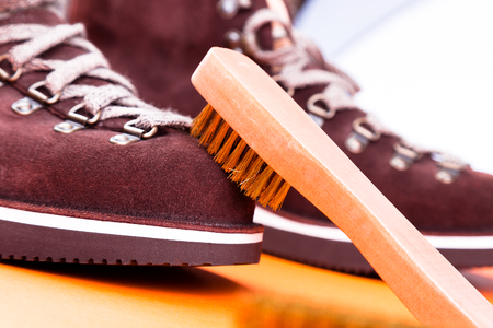 茶色い男性スエード ブーツのブラシ。マクロ。きれいな靴。