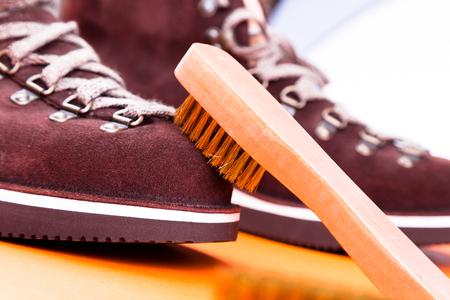 갈색 남자 스웨이드 부츠 브러시입니다. 매크로. 신발을 청소하십시오. 스톡 콘텐츠
