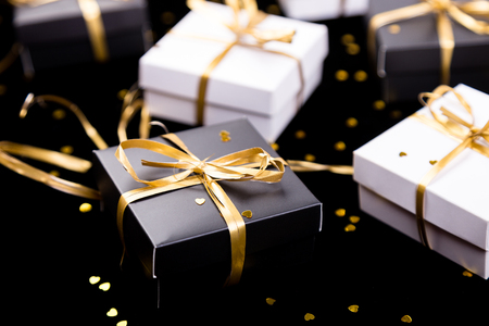 Black and white gift boxes with gold ribbon on shine background. Close up