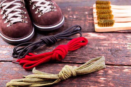 Brown man suede  boots with brush shoelaces on wooden background. Autumn or winter shoes