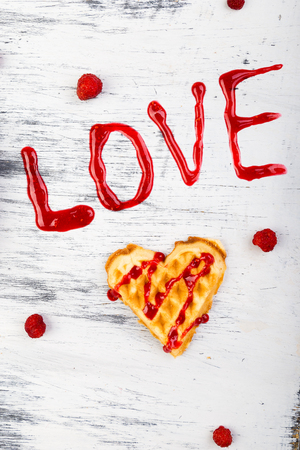 Belgian heart shaped waffle on white background. Word love made by jam