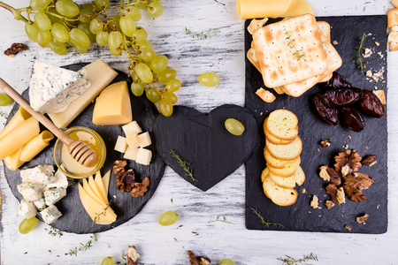 Cheese plate. Assortment of cheese with walnuts, bread an honey on stone slate plate Standard-Bild