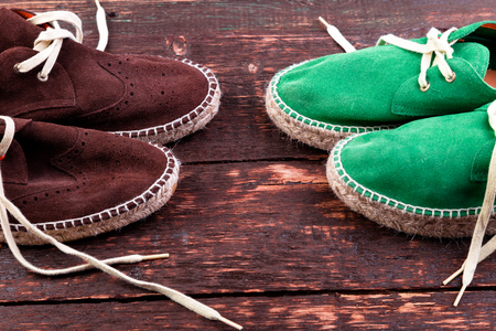 Green and brown suede espadrille shoes on wooden background