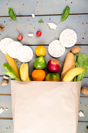 Grocery shopping concept. Different food in paper bag on wooden background.  Flat lay