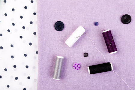 Items for sewing clothes. Sewing buttons, spools of thread and cloth. Top view
