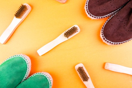 Green and brown suede espadrille shoes with brushes on yellow paper background