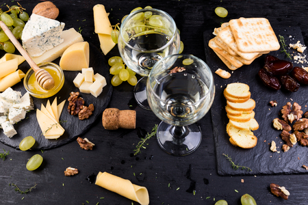 Cheese plate. Assortment of cheese with walnuts, bread an honey on stone slate plate 写真素材