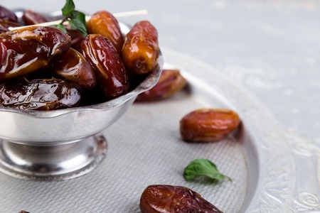 Dry fruit dates on silver tray. Copy space. Close up