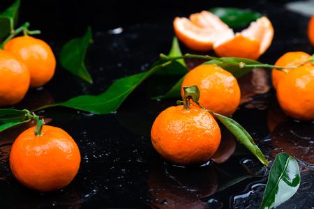 Fresh tangerines Peeled and sliced orange on a Black Background. Citrus background. Wet