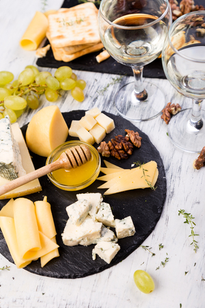 Cheese plate. Assortment of cheese with walnuts, bread an honey on stone slate plate Фото со стока