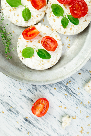 Healthy Rice Cakes with cherry tomatoes, cheese feta, basil and sesame in metal plate on white background. Diet snack.  Top view. Copy space. Stock Photo