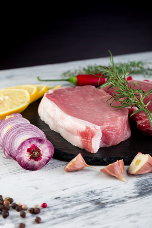 Raw pork meat on black slate plate with spice ingredient - rosemary, ginger, chilli pepper, onion. Stock Photo