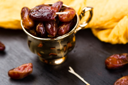 Dry fruit dates in golden cup near slate black heart. Copy space. Stock Photo