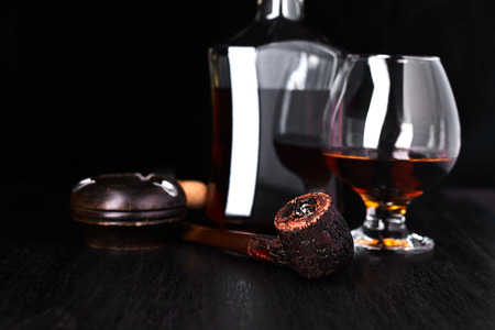 Glass of whiskey with smoking cigar on dark wooden table