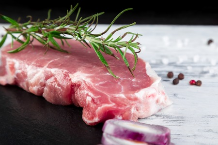 Raw pork meat on black slate plate with spice ingredient - rosemary, ginger, chilli pepper, onion.Top view. Flat lay. Copy space.