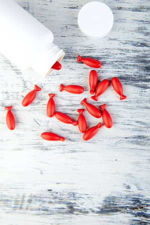 Omega 3 in fish shaped. Red capsules of Fish oil in bottle on white background. Copy space.