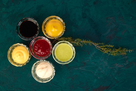 Set of different sauces. Sauces ketchup, mustard, mayonnaise, wasabi, soy sauce in little bowls on green background 스톡 콘텐츠