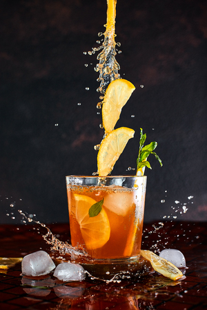 Iced lemon tea on dark background in glass and flying in air ingredients. Levitation effect. Summer cold Iced tea. Food in motion concept. Splash
