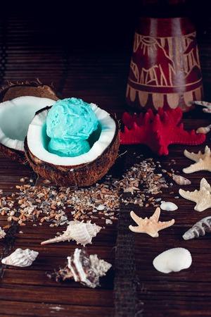 Blue ice cream in coconut bowl near sand, seashells, starfish. Archivio Fotografico